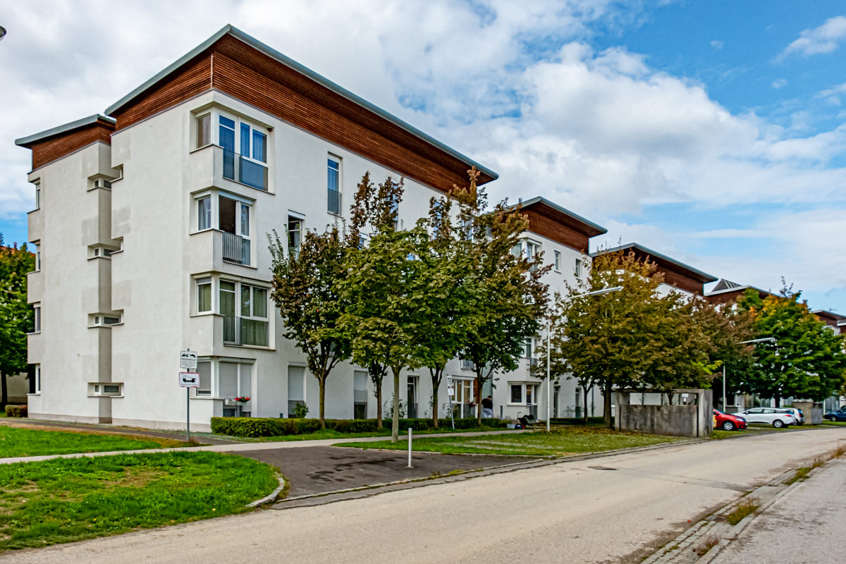 weißer Wohnblock mit Holz und Bäumen