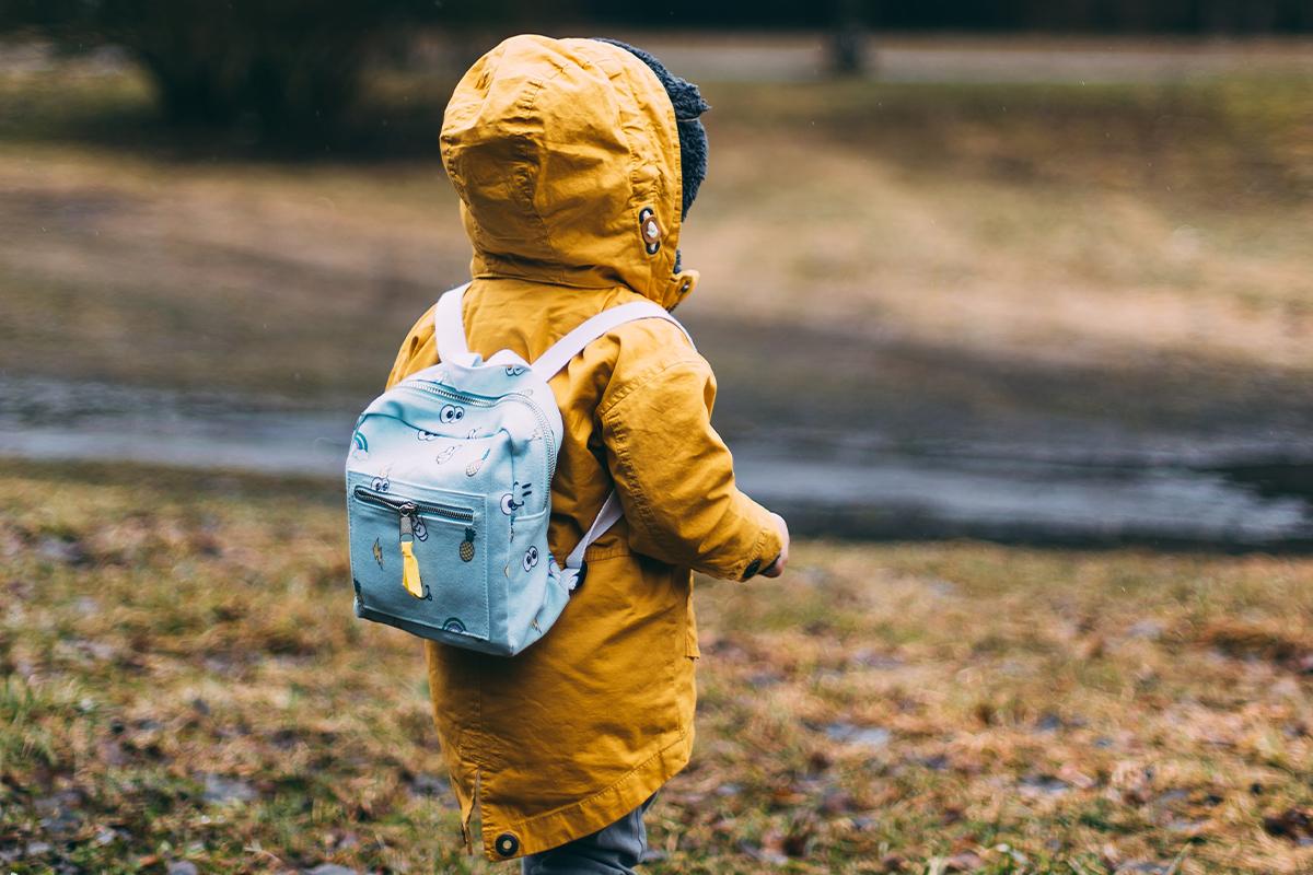 Kleinkind mit gelber Jacke und hellblauen Rucksack