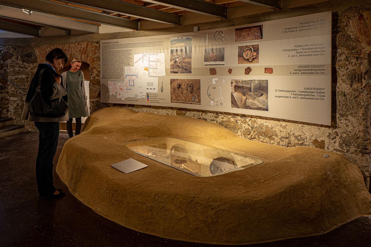 Zwei Personen schauen in eine Glasvitrine, oberhalb an der Wand ist Informationsmaterial angebracht