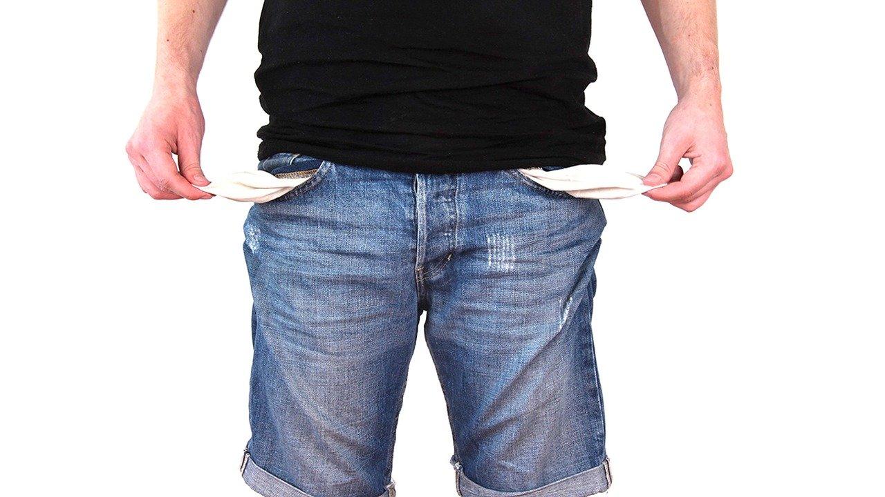 Person mit kurzer blauer Jean und schwarzen T-Shirt zieht die Innentaschen seiner Hose raus um die Leere zu symbolisieren