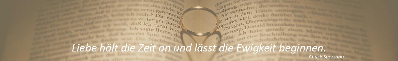 Aufgeschlagenes Buch, in der Mitte einen Ring der einen herzförmigen Schatten wirft, Spruch: Liebe hält die Zeit an und lässt die Ewigkeit beginnen.