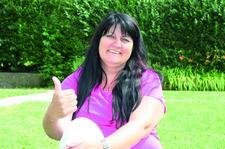 Ilona Rose sitzt in der Wiese und zeigt mit einem Daumen nach oben
