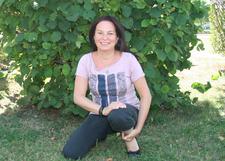 Andrea Friedl in der Hocke vor einem Strauch
