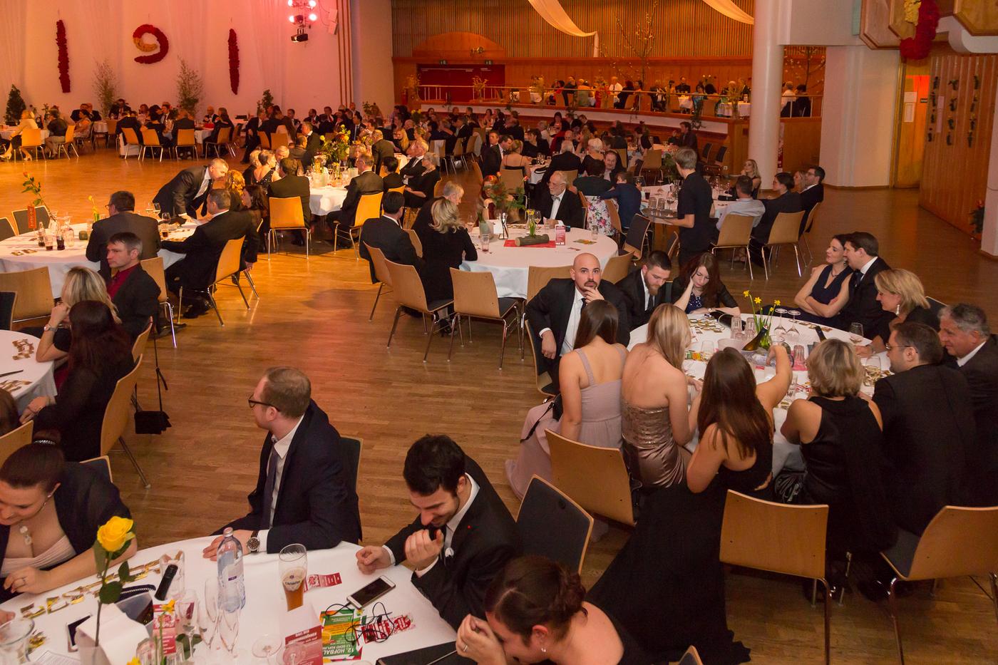 Kürnberghalle von innen mit runden Tischen an denen Personen sitzen