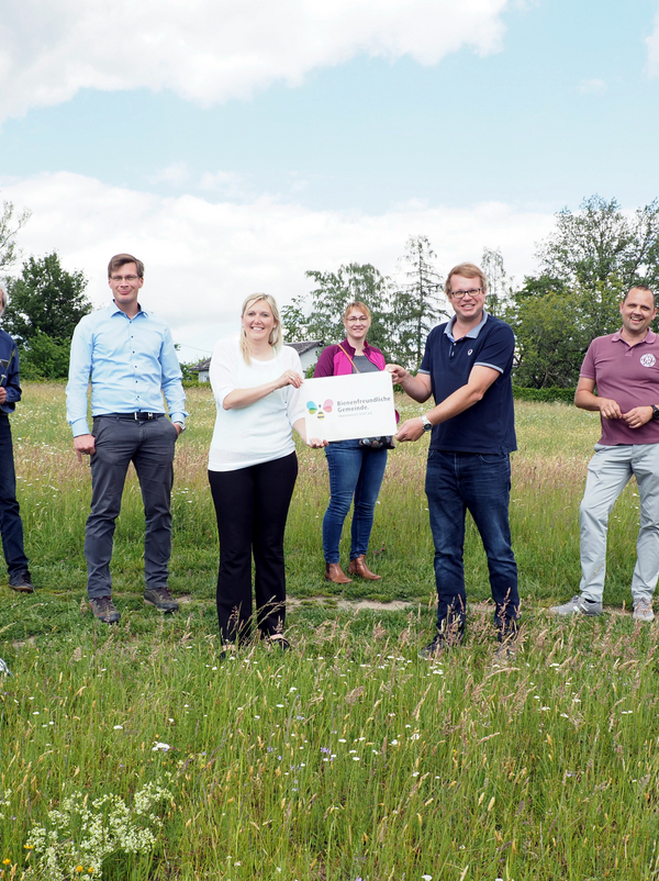 8 Personen in einer Blumenwiese, die vorderen zwei Personen halten ein Schild mit der Aufschrift Bienenfreundliche Gemeinde