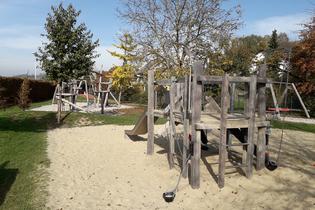 Spielplatz mit großer Sandfläche in der ein Gerüst aus Holz steht