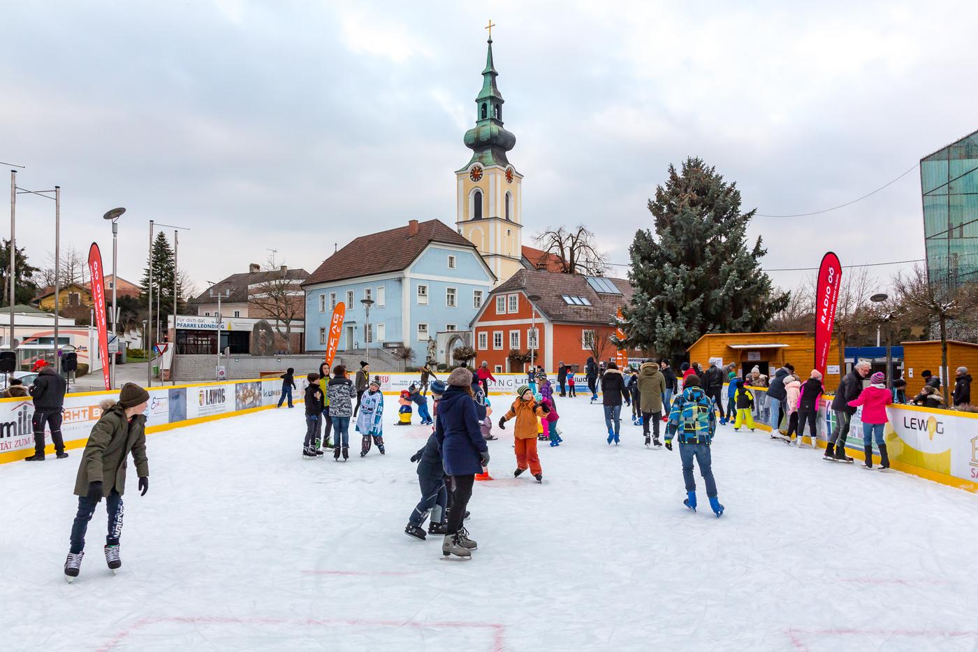 Eislaufplatz mit Kindern, Hintergrund: Kirche und blaues Haus