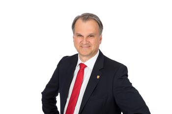 Stadtamtsdirektor Uwe Deutschbauer mit dunkelm Sakko, weißem Hemd und roter Krawatte