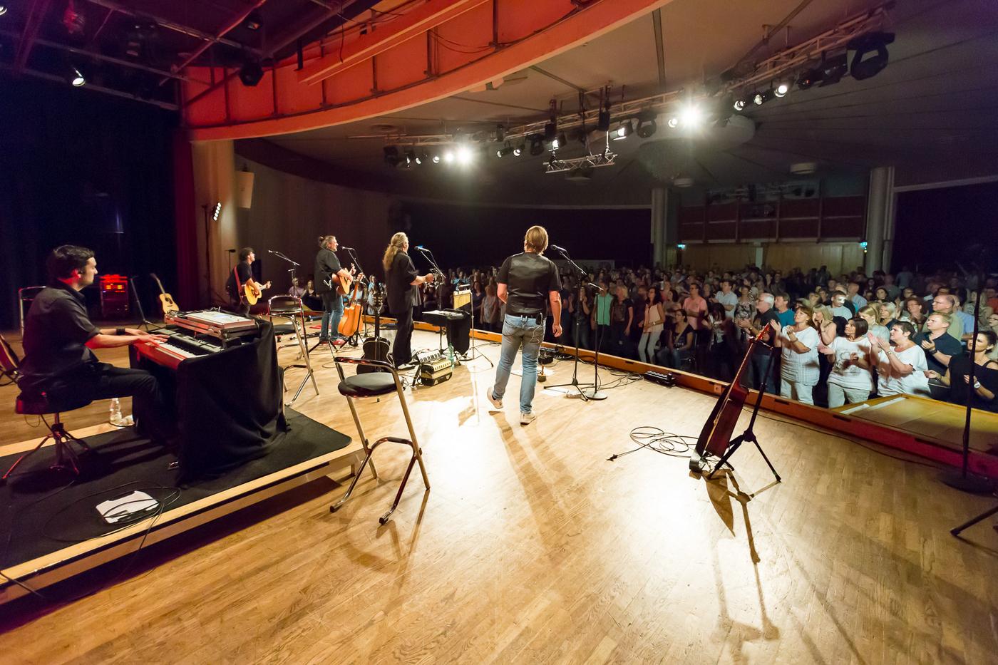Bühne der Kürnberghalle mit Holzboden und drei Musikern