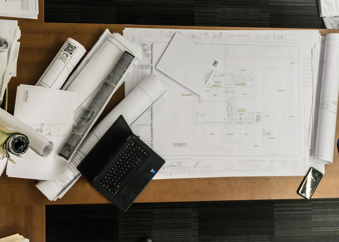 Arbeitsplatz mit diversen Plänen und einem Laptop