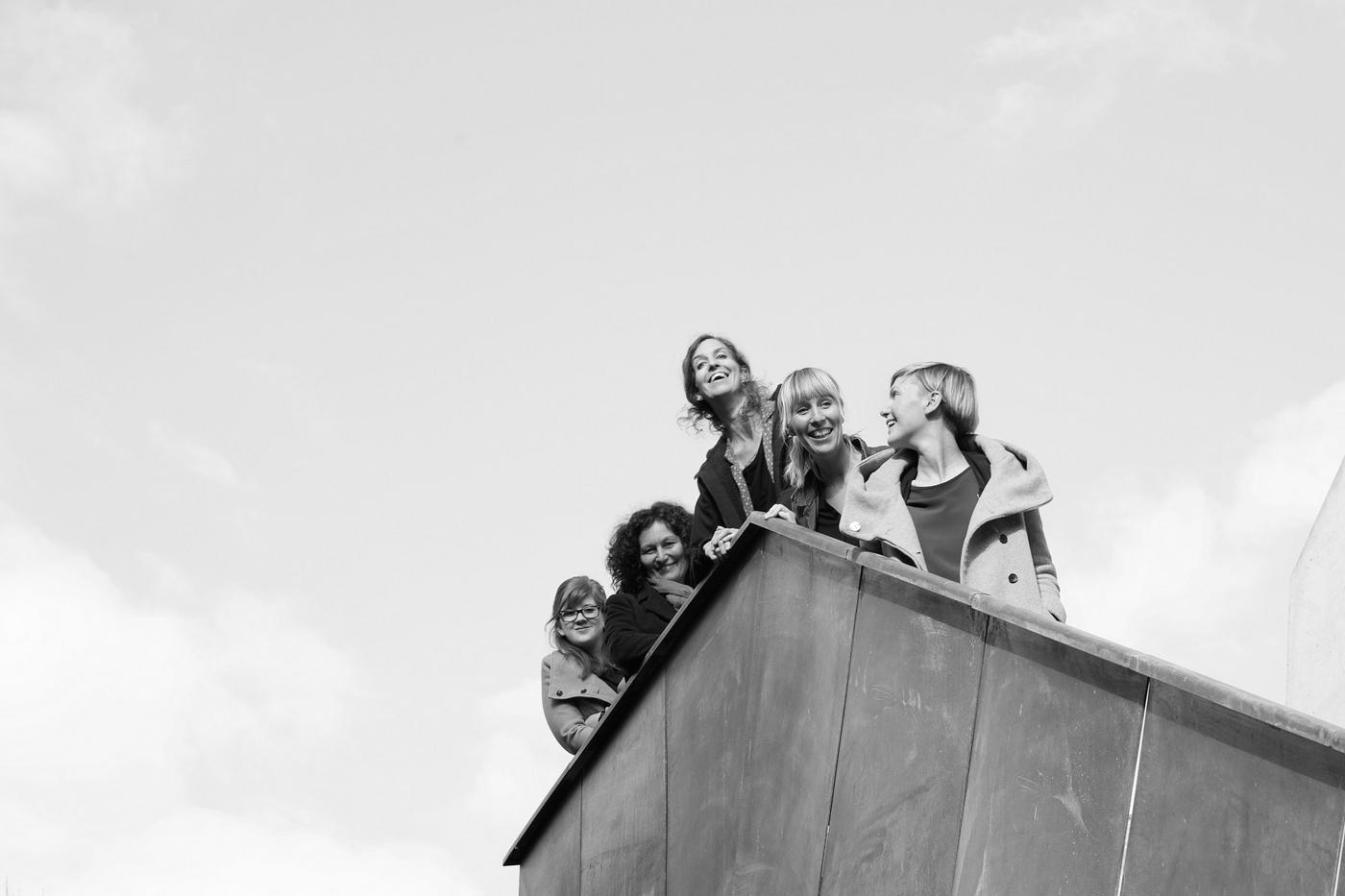 Team der KUVA, an einem Eck eines Flachdaches stehend, Hintergrund Himmel mit Wolken