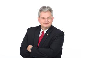 Stadtrat Mag. Harald Kronsteiner mit schwarzen Sakko, weißem Hemd und roter Krawatte