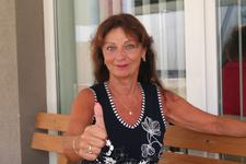 Silvia Rienesl sitzt auf einer Bank und zeigt mit einem Daumen nach oben