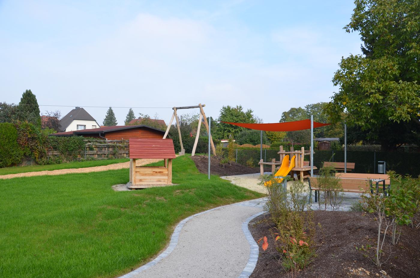 Spielplatz mit gelber Rutsche und einem gepflasterten Weg