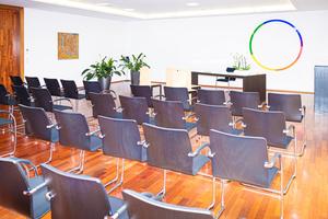 Trauungssaal mit bunten Kreis an der Wand und Stuhlreihen
