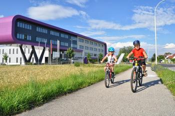 Zwei Kinder mit Fahrrad und Helm auf einem Radweg in Leonding