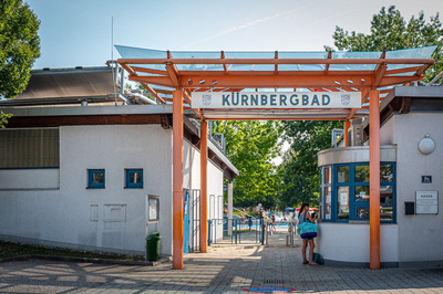 Eingang Kürnbergbad mit oranger Glasüberdachung