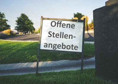 """Hintergrund Straße und Wiese, Vordergrund Tafel mit Aufschrift """"Offene Stellenangebote"""""""