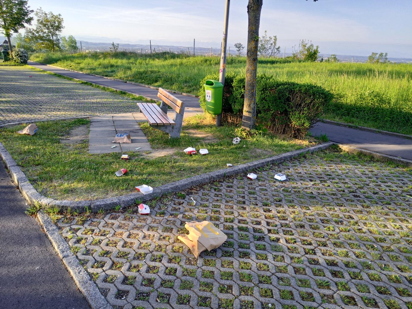 Parkplatz mit einer Bank und einem grünen Mistkübel, Müll liegt am Parkplatz verstreut.
