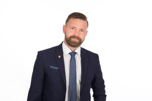 Stadtrat Peter Hametner mit dunklem Sakko, weißem Hemd und blauer Krawatte