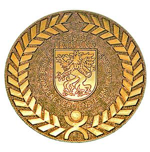 Goldene runde Medaille, in der Mitter das Wappen von Leonding mit einem Drachen
