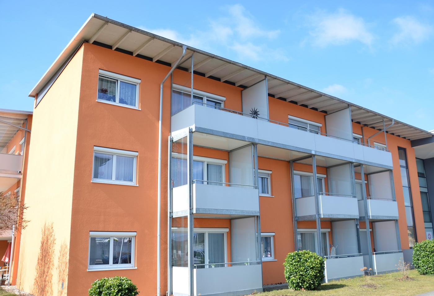 Oranger Wohnblock mit weißen Balkonen