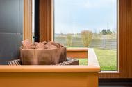Sauna von innen mit Saunaofen und Ausblick ins Grüne
