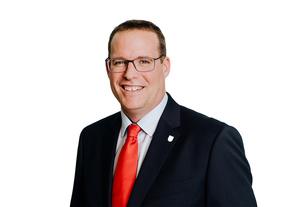 Stadtrat Armin Brunner mit schwarzem Sakko, weißen Hemd und roter Krawatte